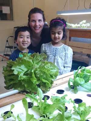 One of our dedicated parent volunteers with students in the aquaponics lab.
