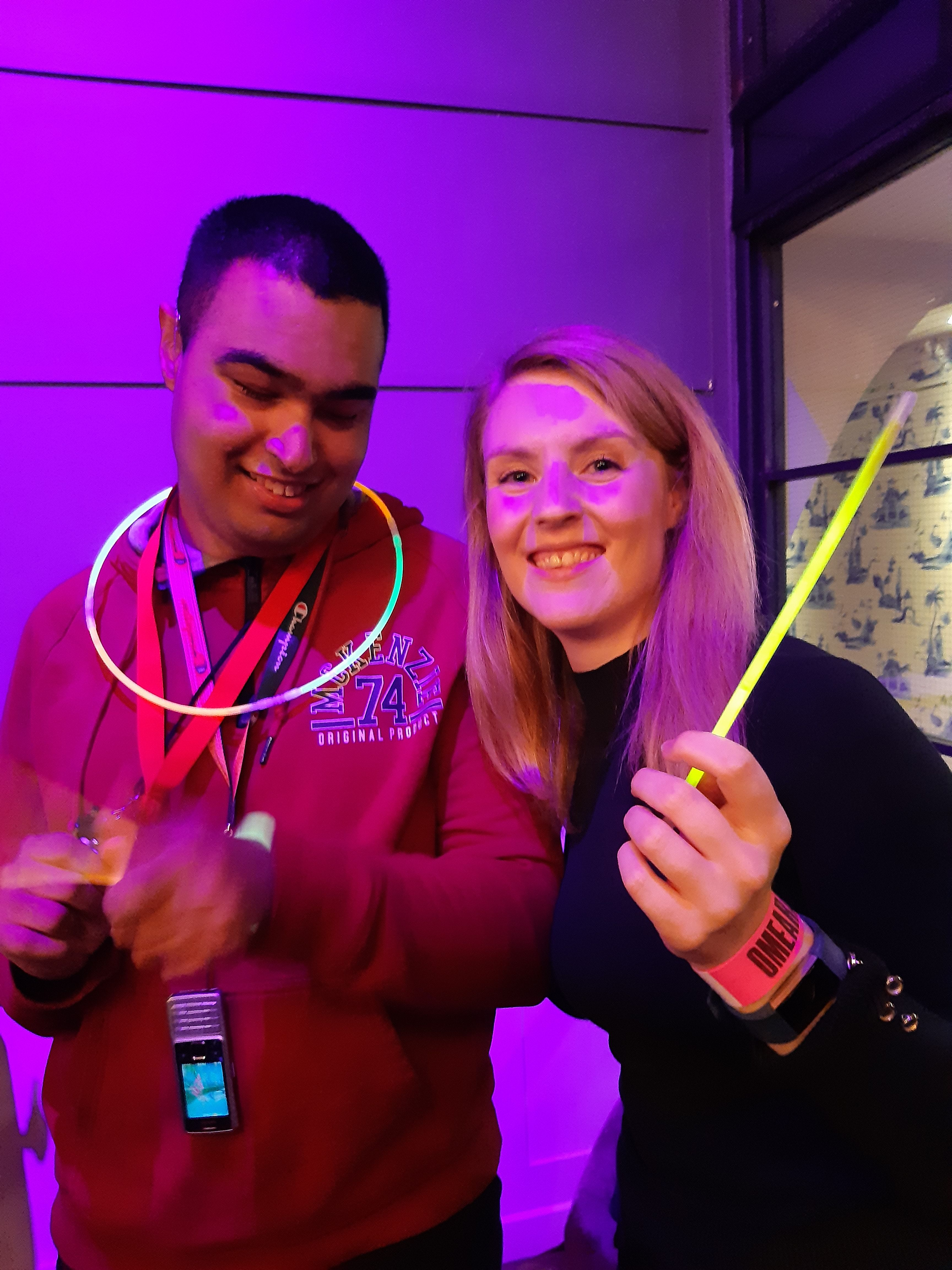 Man with glow stick around his neck and lady holding glow stick stood together in fluorescent light, both smiling