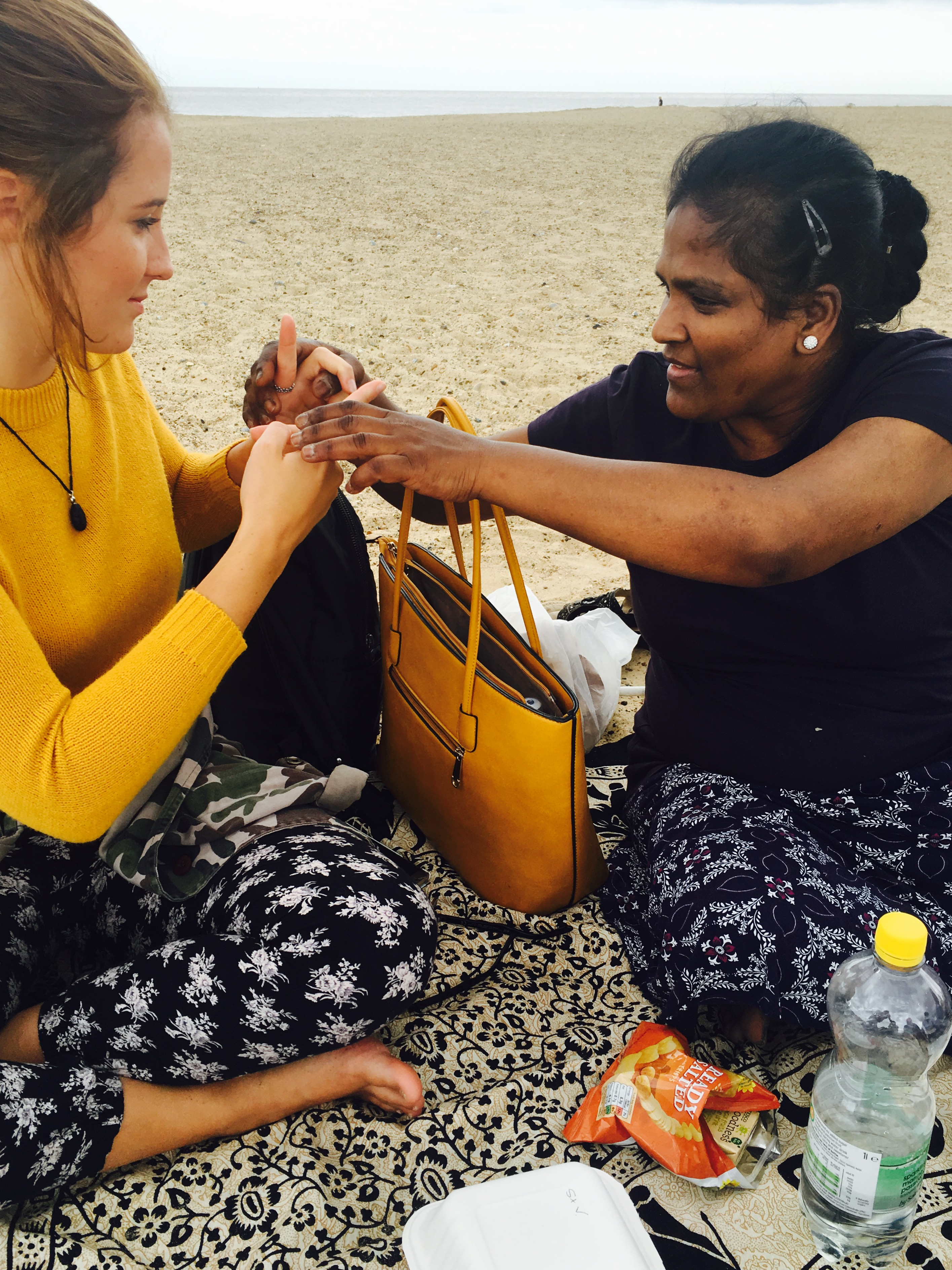 Two ladies sat facing each other with legs crossed on the beach, grasping each other's hands and smiling