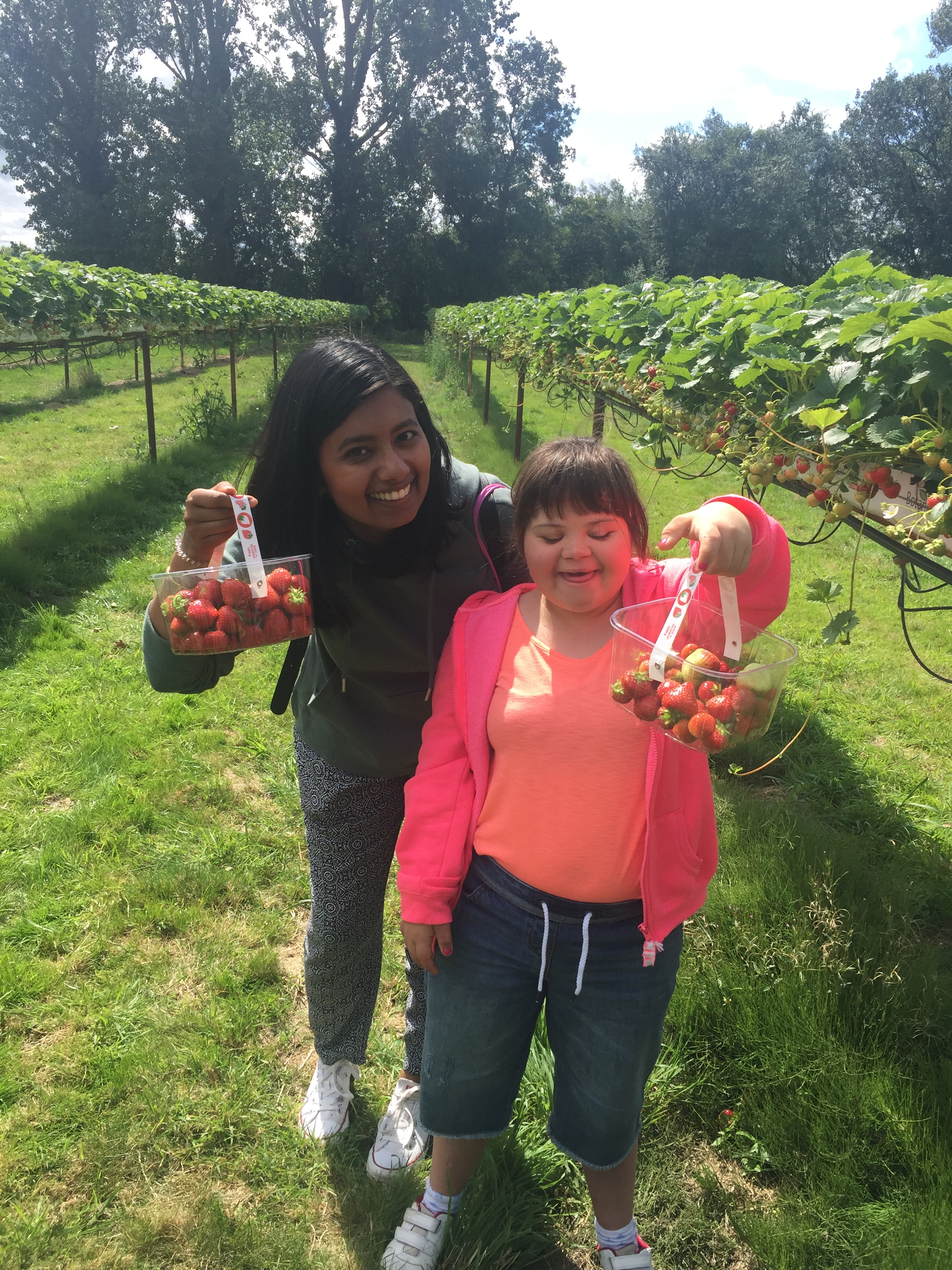 Two ladies standing together in a field smiling and holding full punnets of strawberries