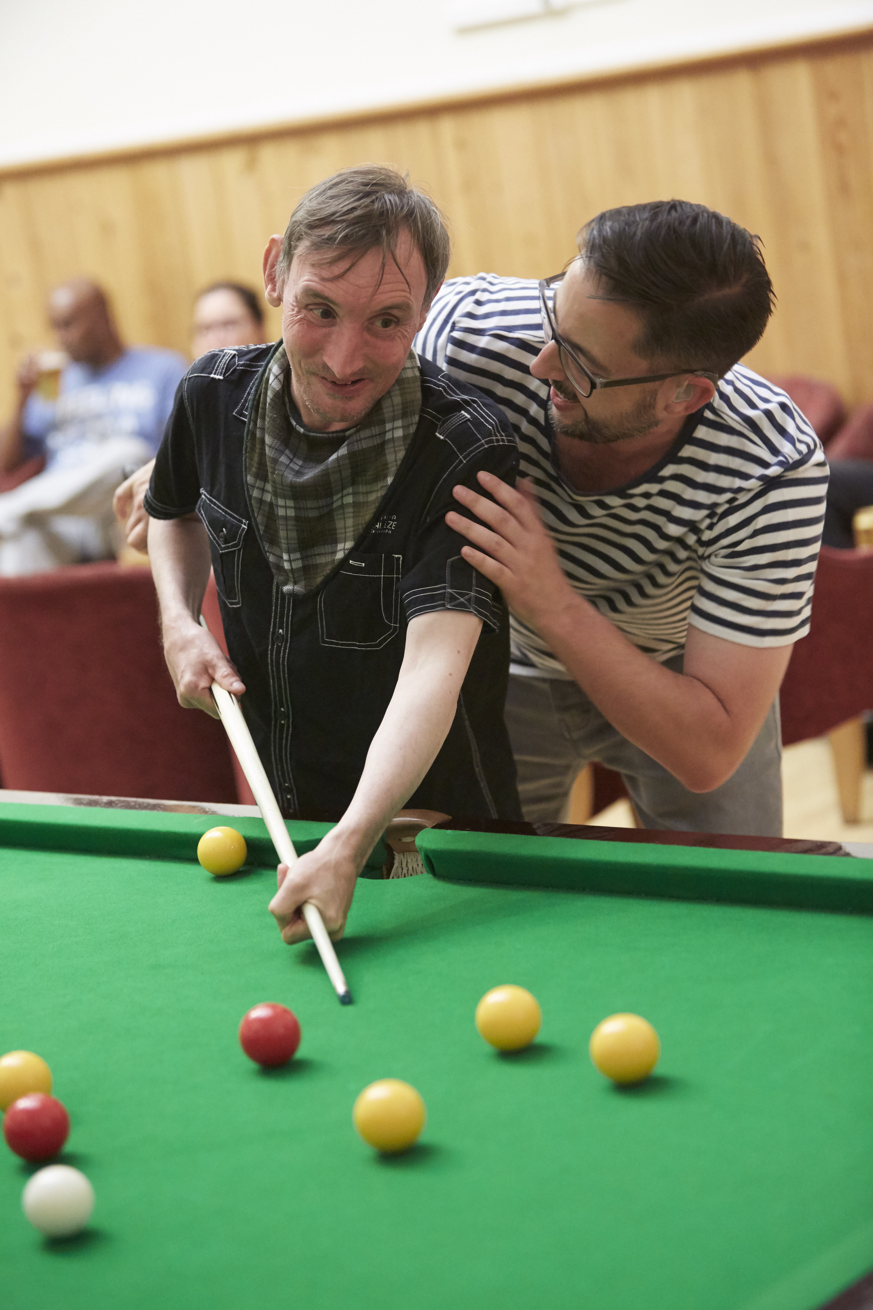 Man holding cue and leaning over pool table with man stood with arm around him leaning down and smiling