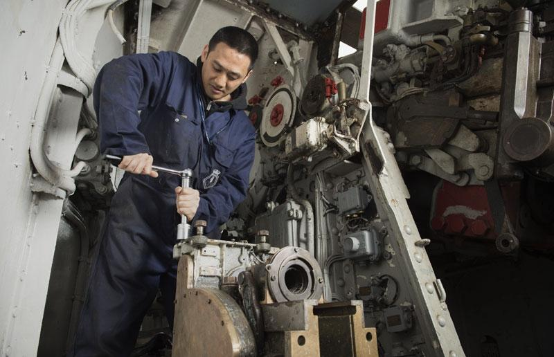 Volunteer conservator works on restoring scuttles in a ship's workshop. © IWM.