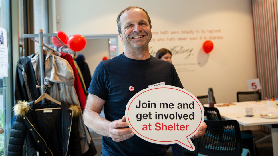 Volunteer holds a sign saying Join Me And Get Involved At Shelter