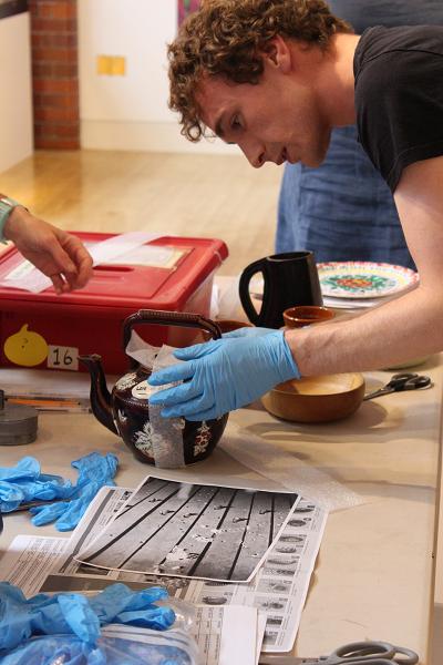 Photograph of a man closely examining a tea pot