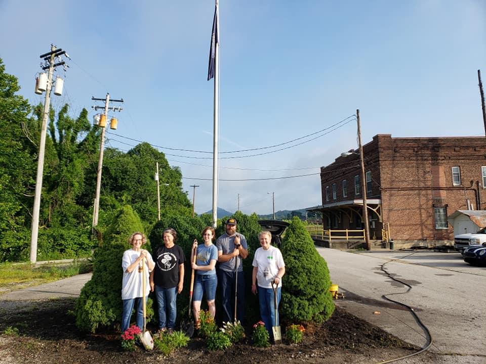 Volunteers stand in a freshly-planted flowerbed