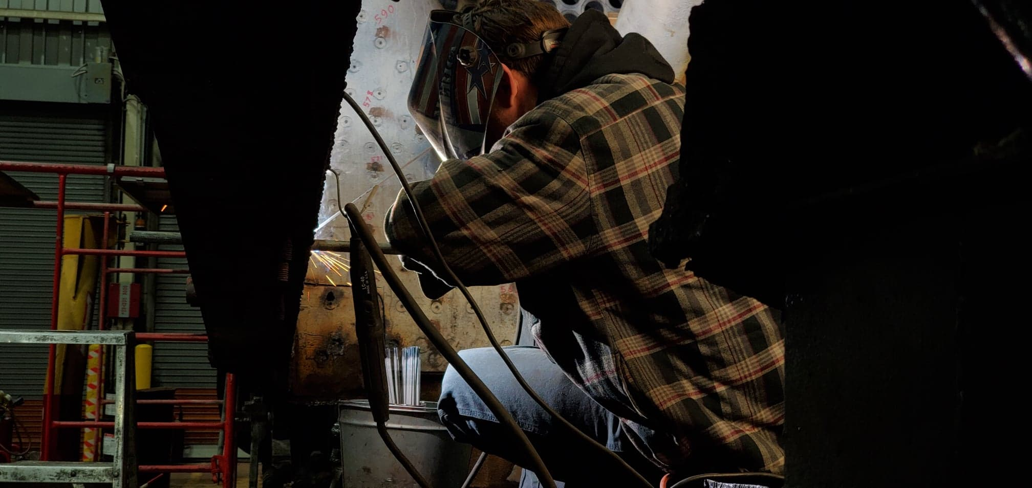 A volunteer makes a weld inside the firebox of the 2716