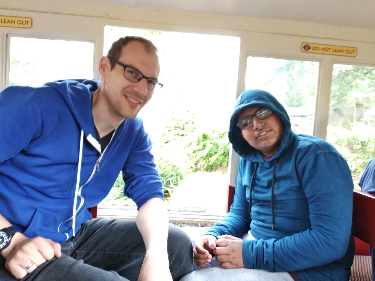 Two men sitting opposite each other on a land train, looking at the camera and smiling