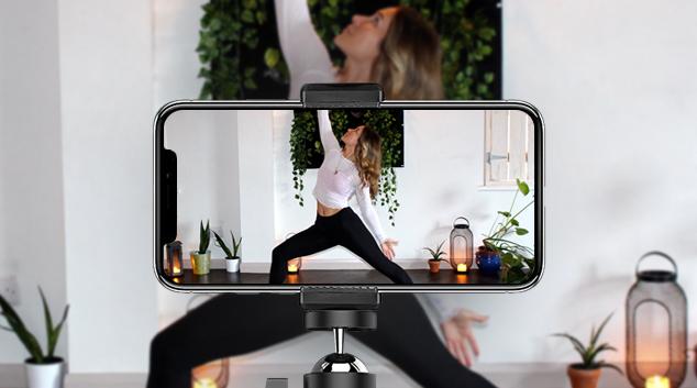 Mobile phone filming woman demonstrating yoga pose.