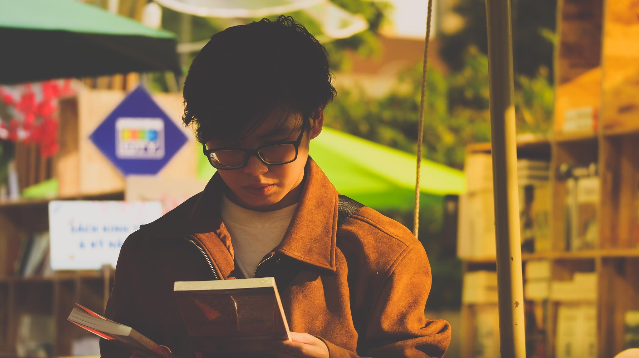 young man reading a book outside
